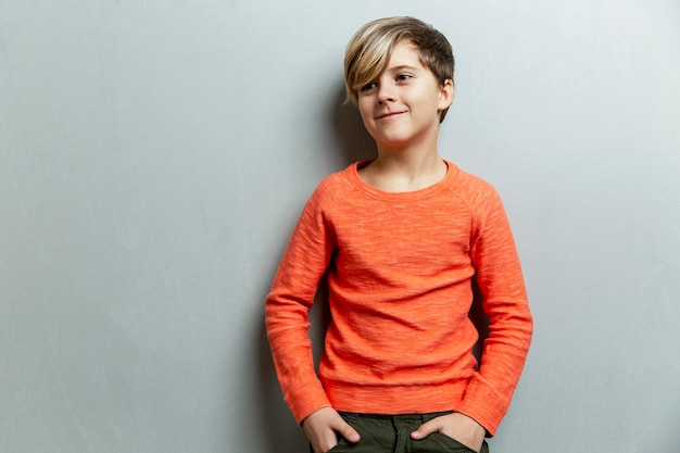 Ein lächelnder junge von 9 jahren mit einer modischen frisur in einem orangefarbenen pullover schaut zur seite