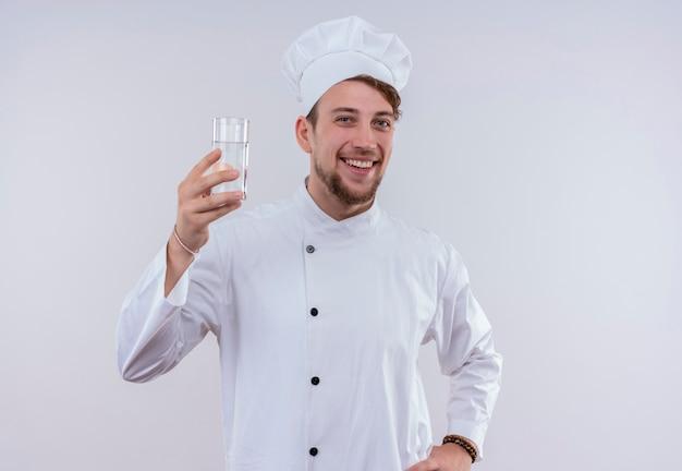 Ein lächelnder junger bärtiger kochmann, der weiße kochuniform und einen hut trägt, der ein glas wasser zeigt, während er auf eine weiße wand schaut
