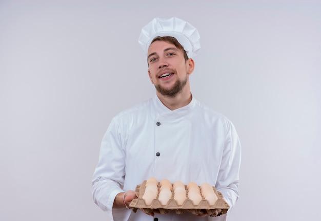 Ein lächelnder junger bärtiger kochmann, der weiße kochuniform und hut trägt, hält einen karton der organischen eier, während auf einer weißen wand betrachtet