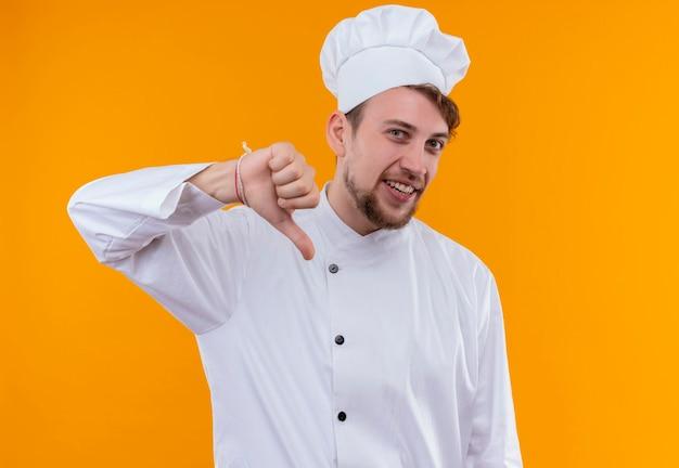 Ein lächelnder junger bärtiger kochmann in der weißen uniform, die daumen unten zeigt, während er auf eine orange wand schaut