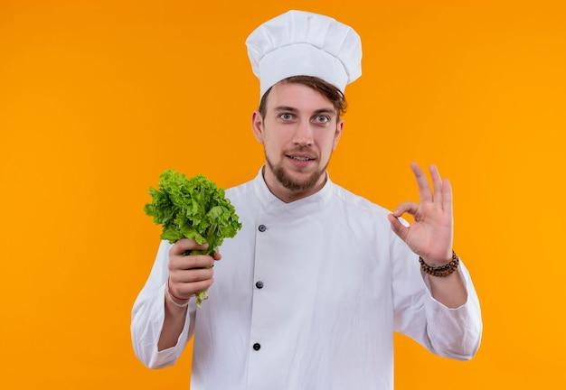 Ein lächelnder junger bärtiger kochmann in der weißen uniform, die grünen blattsalat hält, während auf einer orange wand schaut