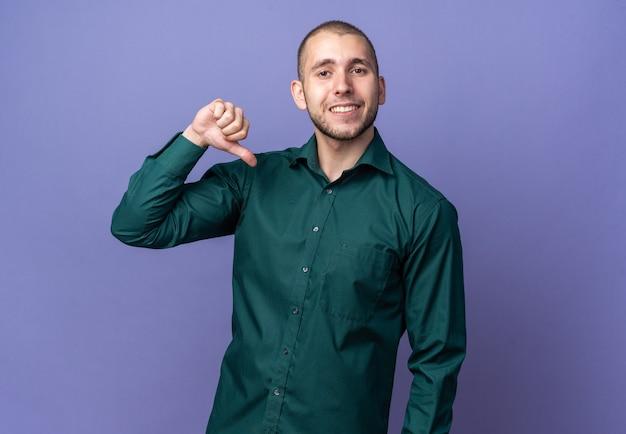 Ein lächelnder junger gutaussehender kerl, der ein grünes hemd trägt, zeigt auf sich selbst