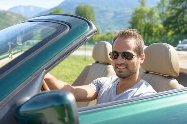 Ein lächelnder junger mann in cabrio