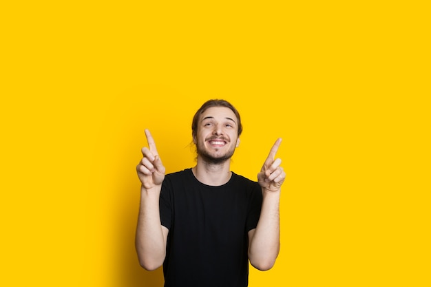 Ein lächelnder kaukasischer mann mit bart und langen haaren zeigt auf den gelben freien raum über ihm