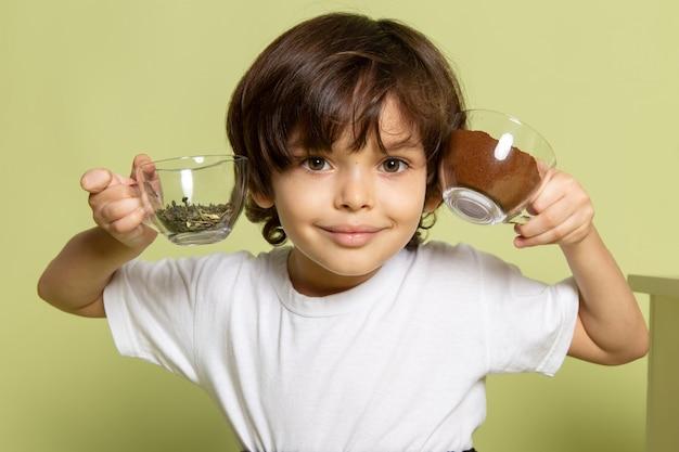 Ein lächelnder kinderjunge der vorderansicht, der kaffee und spezies im weißen t-shirt auf dem steinfarbenen boden hält