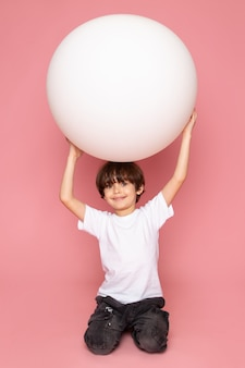 Ein lächelnder kinderjunge der vorderansicht im weißen t-shirt spielt mit weißem ball auf dem rosa raum