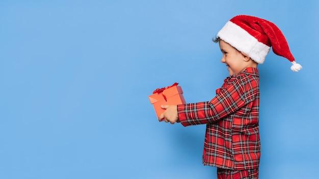 Ein lächelnder kleiner junge im weihnachtspyjama und einem hut mit einer geschenkbox. ein platz für ihren text. studioaufnahme auf blauem hintergrund isoliert. das konzept von neujahr und weihnachten.