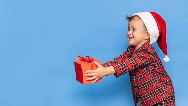 Ein lächelnder kleiner junge im weihnachtspyjama und einen hut mit einer geschenkbox. ein platz für ihren text. studioaufnahme auf blauem hintergrund isoliert. das konzept von neujahr und weihnachten.