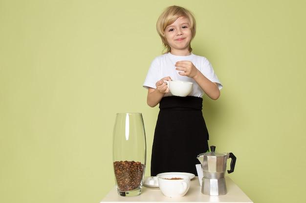 Ein lächelnder kochjunge der vorderansicht, der kaffeegetränk auf dem steinfarbenen schreibtisch vorbereitet