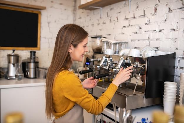 Ein lächelnder langhaariger barista, der eine professionelle kaffeemaschine benutzt