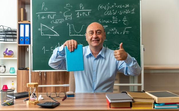Ein lächelnder männlicher lehrer mittleren alters sitzt am tisch mit schulmaterial und hält ein buch, das den daumen im klassenzimmer zeigt