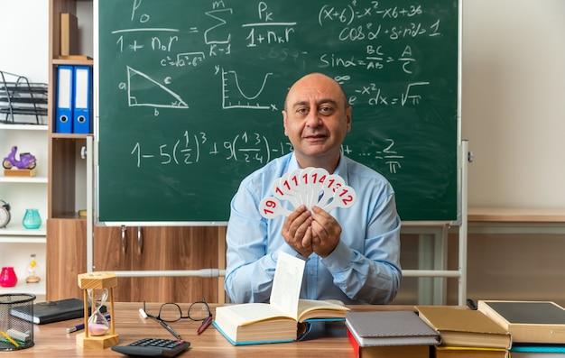 Ein lächelnder männlicher lehrer mittleren alters sitzt am tisch mit schulmaterial und hält zahlenfächer im klassenzimmer