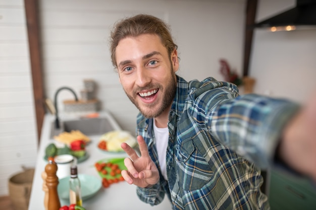 Ein lächelnder mann, der selfie auf seiner küche macht