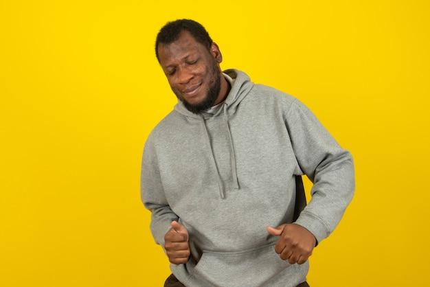 Ein lächelnder mann des afroamerikaners tanzt und posiert auf gelber wand.
