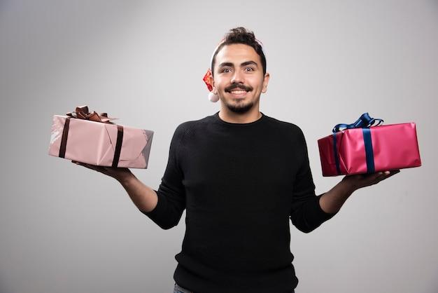 Ein lächelnder mann in einer weihnachtsmannmütze, die neujahrsgeschenke hält.