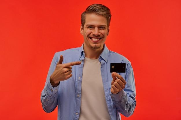 Ein lächelnder mann mit einem bart in einem blauen hemd hält eine schwarze bankkreditkarte und zeigt darauf