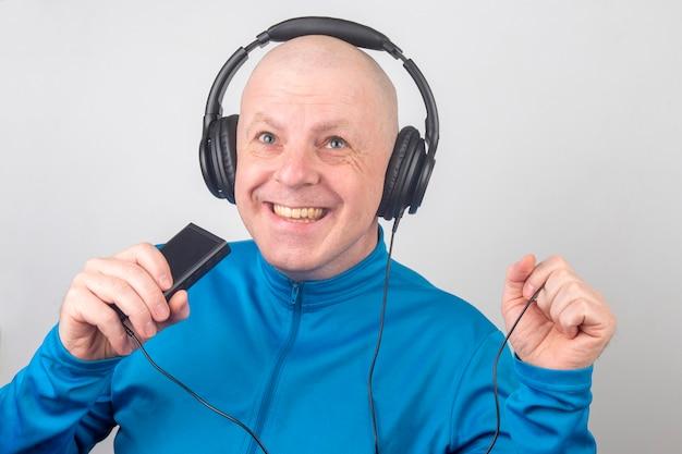 Ein lächelnder mann mit kopfhörern und einem tragbaren digitalen player in der hand entspannt sich, während er seine lieblingsmusik hört
