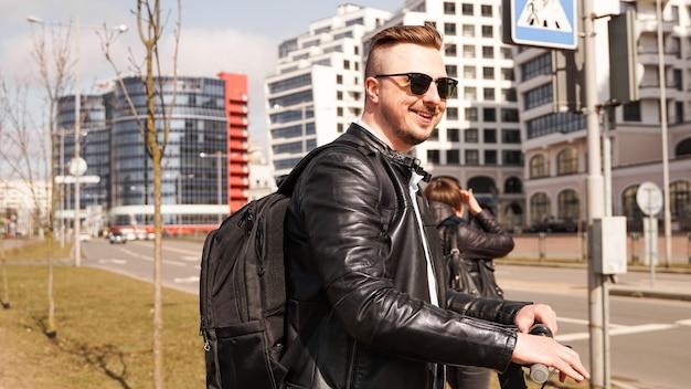 Ein lächelnder mann mit sonnenbrille steht am scheideweg