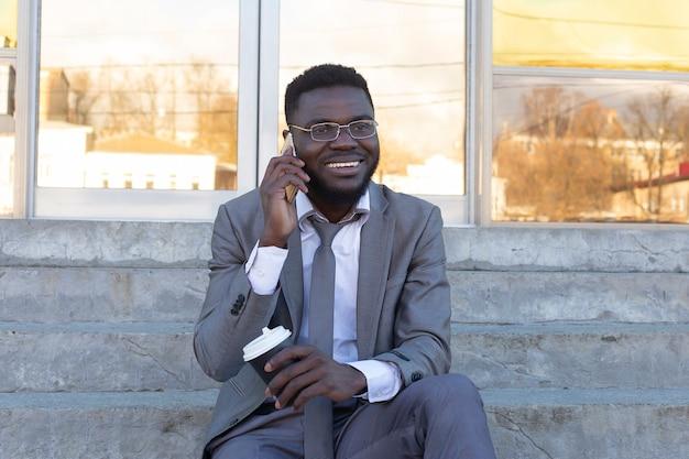 Ein lächelnder mann schreibt sms an freunde am telefon
