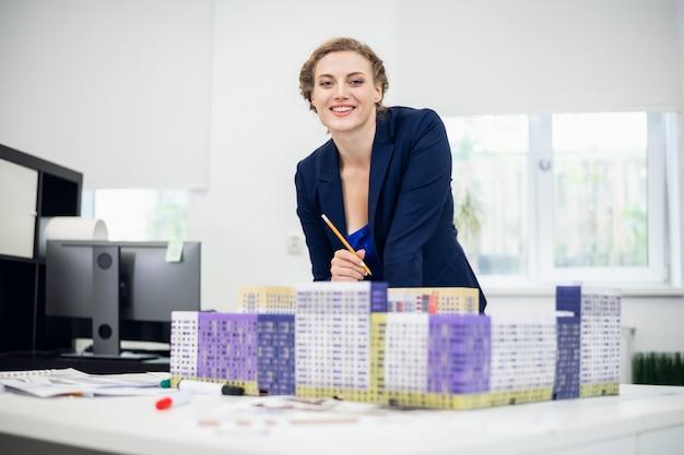 Ein lächelnder mitarbeiter des baubüros, der an einem projekt arbeitet