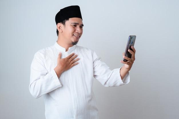 Ein lächelnder muslimischer mann, der einen videoanruf nimmt, um mit seiner familie während des ramadan gegen auf weißer wand zu kommunizieren