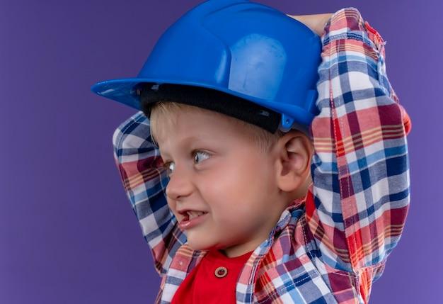 Ein lächelnder niedlicher kleiner junge mit blondem haar, der kariertes hemd hält hand auf blauem helm hält, während seite auf einer lila wand schaut