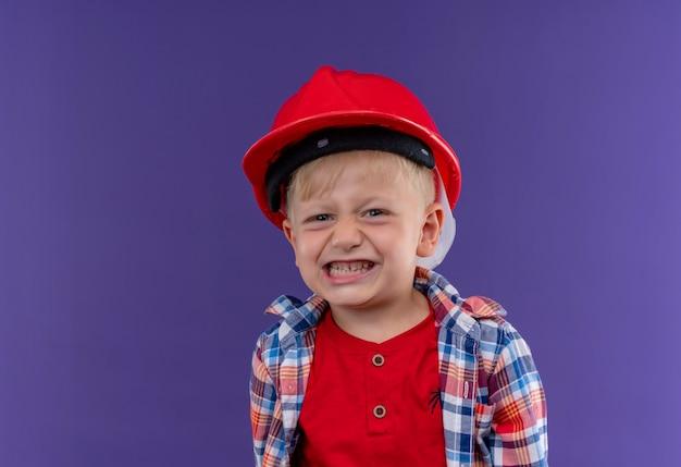 Ein lächelnder niedlicher kleiner junge mit blondem haar, der kariertes hemd im roten helm trägt und auf eine lila wand schaut