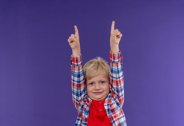 Ein lächelnder niedlicher kleiner junge mit blondem haar, der kariertes hemd trägt, das mit zeigefingern auf eine lila wand zeigt