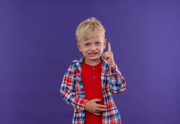 Ein lächelnder niedlicher kleiner junge mit blondem haar, der kariertes hemd trägt, das zeigefinger anhebt, während auf einer lila wand schaut