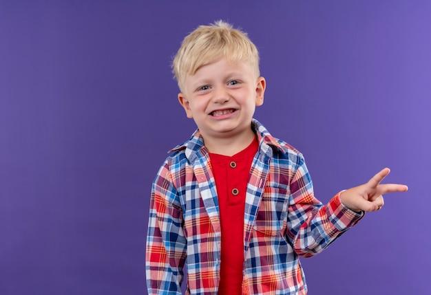 Ein lächelnder niedlicher kleiner junge mit blondem haar, der kariertes hemd trägt, das zwei finger zeigt geste auf einer lila wand