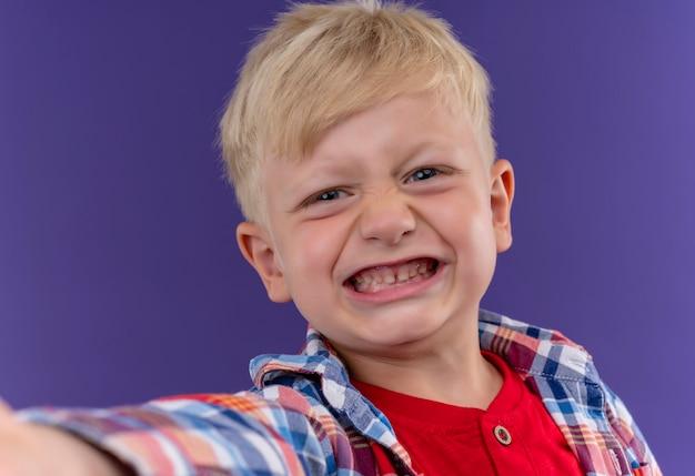 Ein lächelnder niedlicher kleiner junge mit blonden haaren und blauen augen, die kariertes hemd tragen, das auf einer lila wand schaut