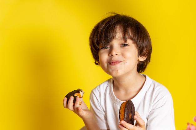 Ein lächelnder süßer junge der vorderansicht, der schoko-donuts im weißen t-shirt auf dem gelben schreibtisch isst