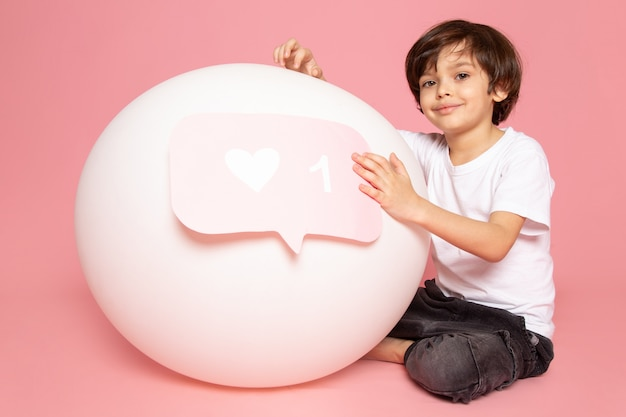 Ein lächelnder süßer junge der vorderansicht im weißen t-shirt, das mit weißem runden ball auf dem rosa raum spielt