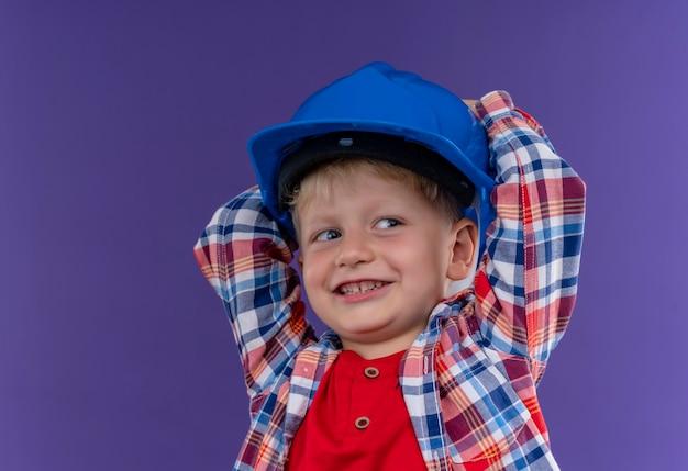 Ein lächelnder süßer kleiner junge mit blondem haar, der kariertes hemd hält, das hand auf blauem helm auf einer lila wand hält