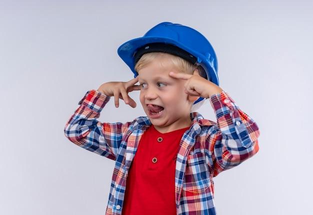 Ein lächelnder süßer kleiner junge mit blondem haar, der kariertes hemd im blauen helm trägt, der mit zeigefinger auf einer weißen wand auf seinen kopf zeigt
