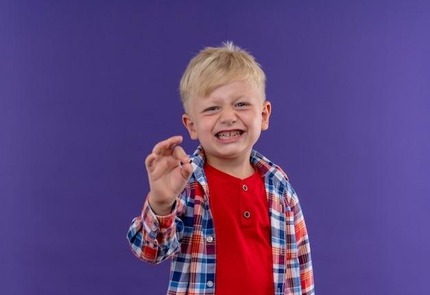 Ein lächelnder süßer kleiner junge mit blondem haar, der kariertes hemd trägt, das ok geste zeigt, die auf einer lila wand schaut