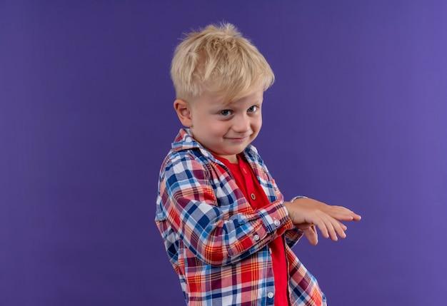 Ein lächelnder süßer kleiner junge mit blondem haar, der kariertes hemd trägt und seine hände hochhält, während er auf eine lila wand schaut