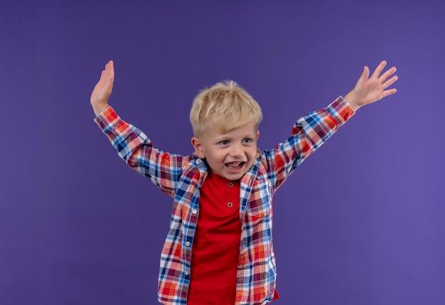 Ein lächelnder süßer kleiner junge mit blondem haar, der kariertes hemd trägt und seine hände in der luft hält, während er auf eine lila wand schaut