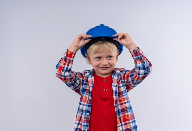 Ein lächelnder süßer kleiner junge mit blondem haar, der kariertes hemd trägt und seinen blauen helm mit den händen auf kopf auf einer weißen wand hält