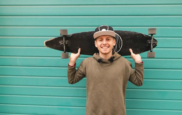 Ein lächelnder teenager in einer mütze und einem hoodie steht auf dem hintergrund einer grünen wand und hält ein longboard an seiner schulter