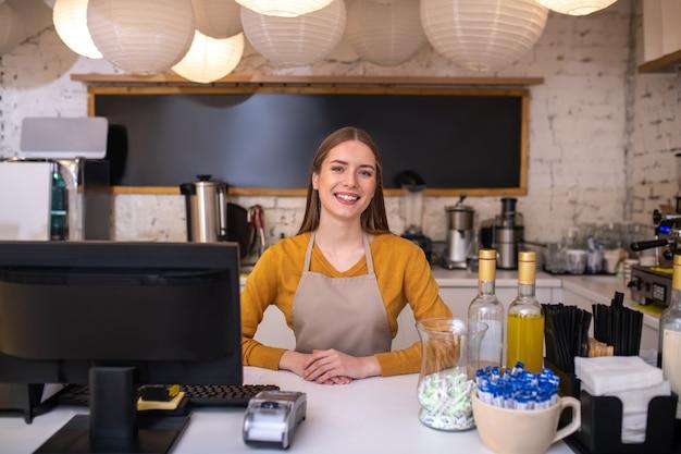 Ein lächelnder und fröhlicher caféangestellter, der auf kunden wartet