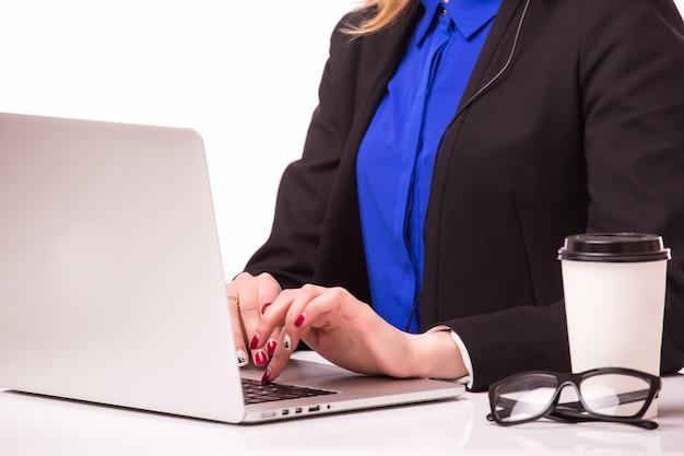 Ein lächelndes junges kundendienstmädchen mit einem headset an ihrem arbeitsplatz