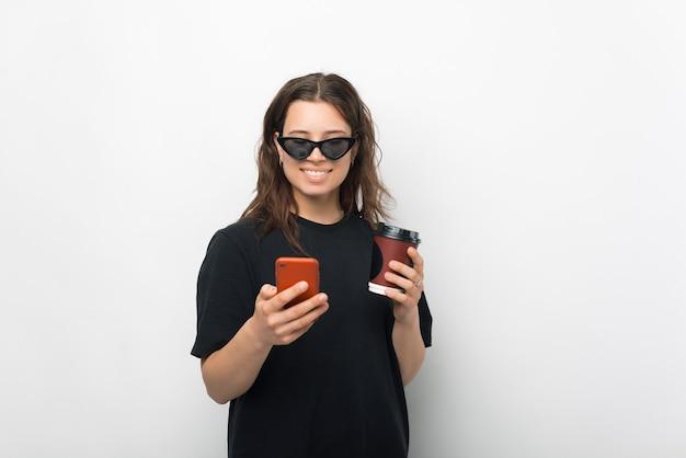 Ein lächelndes junges mädchen, das mit jemandem auf ihrem telefon chattet, trinkt kaffee mit sonnenbrille