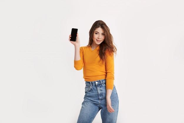 Ein lächelndes junges mädchen hält ein smartphone in ihren händen. porträt eines mädchens mit einem telefon in ihren händen auf einem hellen hintergrund mit platz für text
