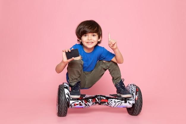 Ein lächelndes kind der vorderansicht im blauen t-shirt, das segway auf dem rosa boden reitet
