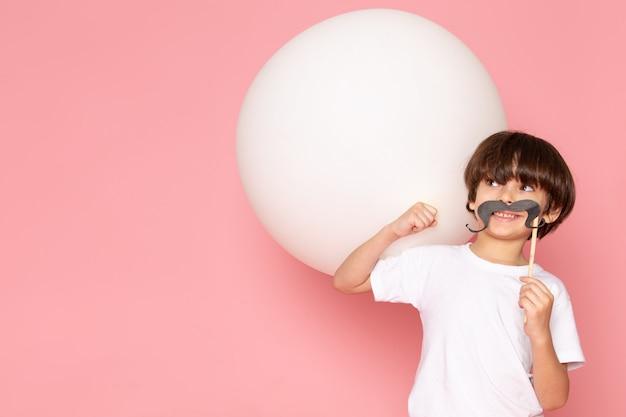 Ein lächelndes kleines kind der vorderansicht im weißen t-shirt, das weißen ball auf dem rosa boden hält
