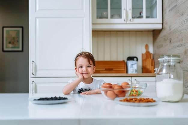 Ein lächelndes kleines mädchen, das am küchentisch sitzt, wo es zutaten für die herstellung eines kuchens gibt