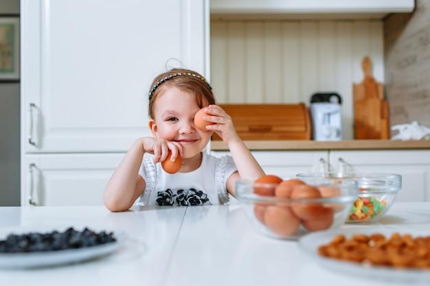 Ein lächelndes kleines mädchen sitzt am küchentisch, wo es zutaten für die herstellung eines kuchens gibt