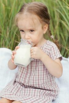 Ein lächelndes kleines mädchen trinkt an einem sommertag an der frischen luft milch aus einem krug auf einem feld mit grünem gras.