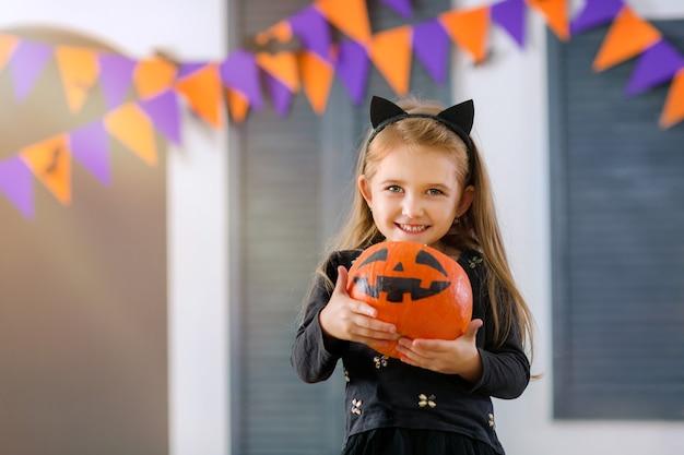 Ein lächelndes mädchen im karnevalskostüm einer kleinen katze spielt mit kürbis und süßigkeiten im zimmer
